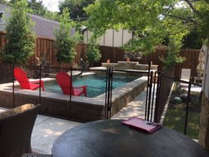 Bronze pool fence has a flexible swing piece to keep the dogs out of the garden.
